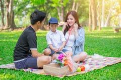 Momento feliz de la comida campestre del día de fiesta del niño adolescente asiático de la familia una Fotografía de archivo libre de regalías
