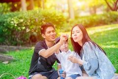 Momento feliz de la comida campestre del día de fiesta del niño adolescente asiático de la familia una en el parque Foto de archivo libre de regalías