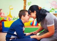 Momento pieno di sentimento ritratto della madre e di suo figlio caro con l'inabilità nel centro di riabilitazione Fotografia Stock