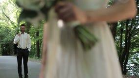 Momento romántico, novia y novio de la boda permaneciendo en el parque en la puesta del sol almacen de metraje de vídeo