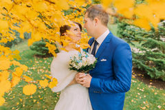 Momento romántico de pareja nuevamente casada debajo del árbol del otoño con las hojas amarillas Imagen de archivo libre de regalías