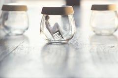 Momento surreale di una donna minuscola che si siede su una sedia dentro un vaso di vetro nella tavola a casa fotografia stock
