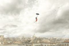 Momento surrealista de un vuelo de la mujer con su paraguas sobre la ciudad imágenes de archivo libres de regalías