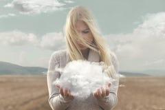 Momento surrealista, mujer que sostiene en sus manos una nube suave imagenes de archivo
