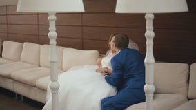 Momento tenero del primo piano delle coppie felici di nozze che si rilassano e che baciano morbidamente sul sofà bianco nel caffè archivi video