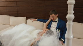 Momento tenero del primo piano delle coppie felici di nozze che si rilassano sul sofà bianco nel caffè lussuoso archivi video