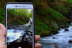 momentopname van waterval in bergbos op het telefoonscherm die op natuurlijke achtergrond in hand wordt gehouden Karpatisch, clos royalty-vrije stock fotografie