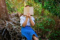 Momentos de relaxamento, jovem mulher feliz que lê um livro no fundo da natureza foto de stock royalty free