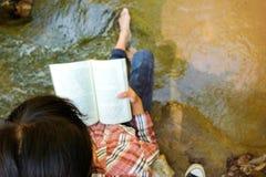 Momentos de relaxamento, jovem mulher feliz que lê um livro no fundo da natureza imagem de stock
