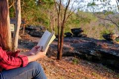 Momentos de relaxamento, jovem mulher que lê um livro no fundo da natureza Abrandamento de solo, cor do tom do moderno imagens de stock