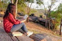Momentos de relaxamento, jovem mulher que lê um livro no fundo da natureza Abrandamento de solo, cor do tom do moderno fotos de stock