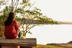 Momentos de relaxamento, jovem mulher que lê um livro no fundo da natureza Abrandamento de solo, cor do tom do moderno imagens de stock royalty free