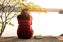 Momentos de relaxamento, jovem mulher que lê um livro no fundo da natureza Abrandamento de solo, cor do tom do moderno foto de stock royalty free