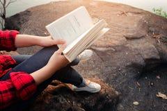 Momentos de relaxamento, jovem mulher que lê um livro no fundo da natureza Abrandamento de solo, cor do tom do moderno imagem de stock royalty free