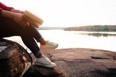 Momentos de relaxamento, jovem mulher que lê um livro no fundo da natureza Abrandamento de solo, cor do tom do moderno imagem de stock