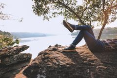Momentos de relaxamento, relaxamento novo asiático do menino exterior no lago no por do sol Relaxe o tempo no curso do conceito d imagens de stock