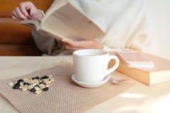 Momentos de relaxamento, xícara de café e um livro na tabela de madeira em n foto de stock royalty free