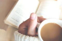 Momentos de relaxamento, xícara de café e um livro na tabela de madeira no fundo da natureza, cor do tom do vintage e foco macio foto de stock