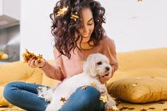 Momentos doces felizes da mulher bonita nova com o cabelo encaracolado moreno cortado que tem o divertimento com o cão em ouropéi imagens de stock