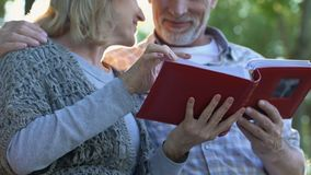 Momentos felices, padres adultos que admiran las fotos en el álbum de la familia que recuerda la juventud metrajes