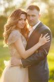 Momentos románticos de un par joven de la boda en prado del verano Imágenes de archivo libres de regalías