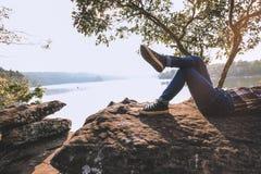 Moments de détente, jeune détente asiatique de garçon extérieure sur le lac dans le coucher du soleil Détendez le temps sur le vo Images stock