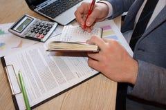 Moments fonctionnants Écriture de jeune homme dans son carnet tout en se reposant à son lieu de travail devant la fenêtre image libre de droits