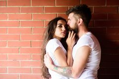 Moments of intimacy. Couple in love hugs brick wall background. Couple find place to be alone. Girl and hipster romantic. Date intimacy moment. Couple enjoy royalty free stock image
