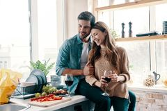 Moments of intimacy. Beautiful young couple cooking dinner and drinking wine while standing in the kitchen at home royalty free stock photography