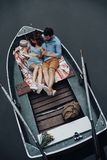 Moments of intimacy. Top view of beautiful young women reading book while sitting in the boat with her boyfriend stock photos