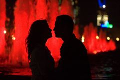 Moments of life. Night shot - sillouettes of woman and man kissing. Red fountains after them - lights of Moscow city royalty free stock photo