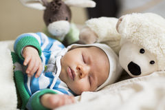 Moments of tranquility: Lovely baby boy sleeping. Resting time: Sweet peaceful baby boy sleeping during day time surrounded by toys Stock Photos