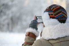 Moments of winter. Women in winter clothing, fingerless mittens and ornamented hat photographing snowy forest by a mobile phone. Shallow dof. Focus on hand Royalty Free Stock Photos