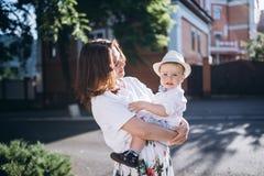 Momhold joven hermoso su hijo Mirada de la mujer al hijo, son ambos sensación feliz fotos de archivo