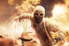 Momia asustadiza en un desierto en la puesta del sol Foto de archivo