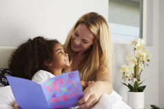 Momia caucásica e hija negra, mirando uno a foto de archivo