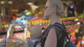 Momia con el bebé que camina en el funfair almacen de metraje de vídeo