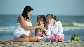 Momia con el daughterd que se relaja en la playa almacen de video