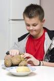 Momia de ayuda del muchacho en cocina Imagen de archivo