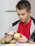 Momia de ayuda del muchacho en cocina Foto de archivo libre de regalías
