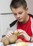 Momia de ayuda del muchacho en cocina Fotografía de archivo libre de regalías