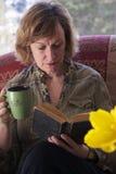 Momia del nacido en el baby boom que toma una rotura y que lee un libro Fotografía de archivo