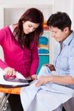 Momia e hija durante planchar Imagen de archivo libre de regalías