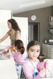 Momia e hijas que se lavan para arriba en cocina Imagenes de archivo