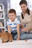 Momia e hijo con el conejo del animal doméstico en el país Imagenes de archivo