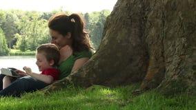 Momia e hijo que juegan debajo de un árbol