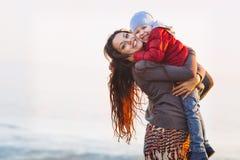 Momia feliz y bebé que caminan en la playa en otoño Imagen de archivo