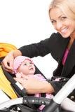 Momia hermosa joven con el bebé en cochecito niño de abrazo rubio hermoso y sonrisa fotos de archivo libres de regalías