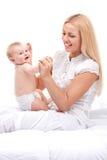 Momia joven que detiene al pequeño bebé sentada rubia hermosa en cama y la sonrisa imagen de archivo
