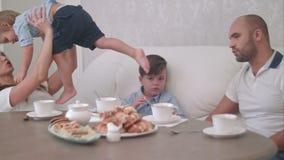 Momia joven que juega con su bebé mientras que papá que habla con su hijo que se sienta en la tabla de té almacen de video